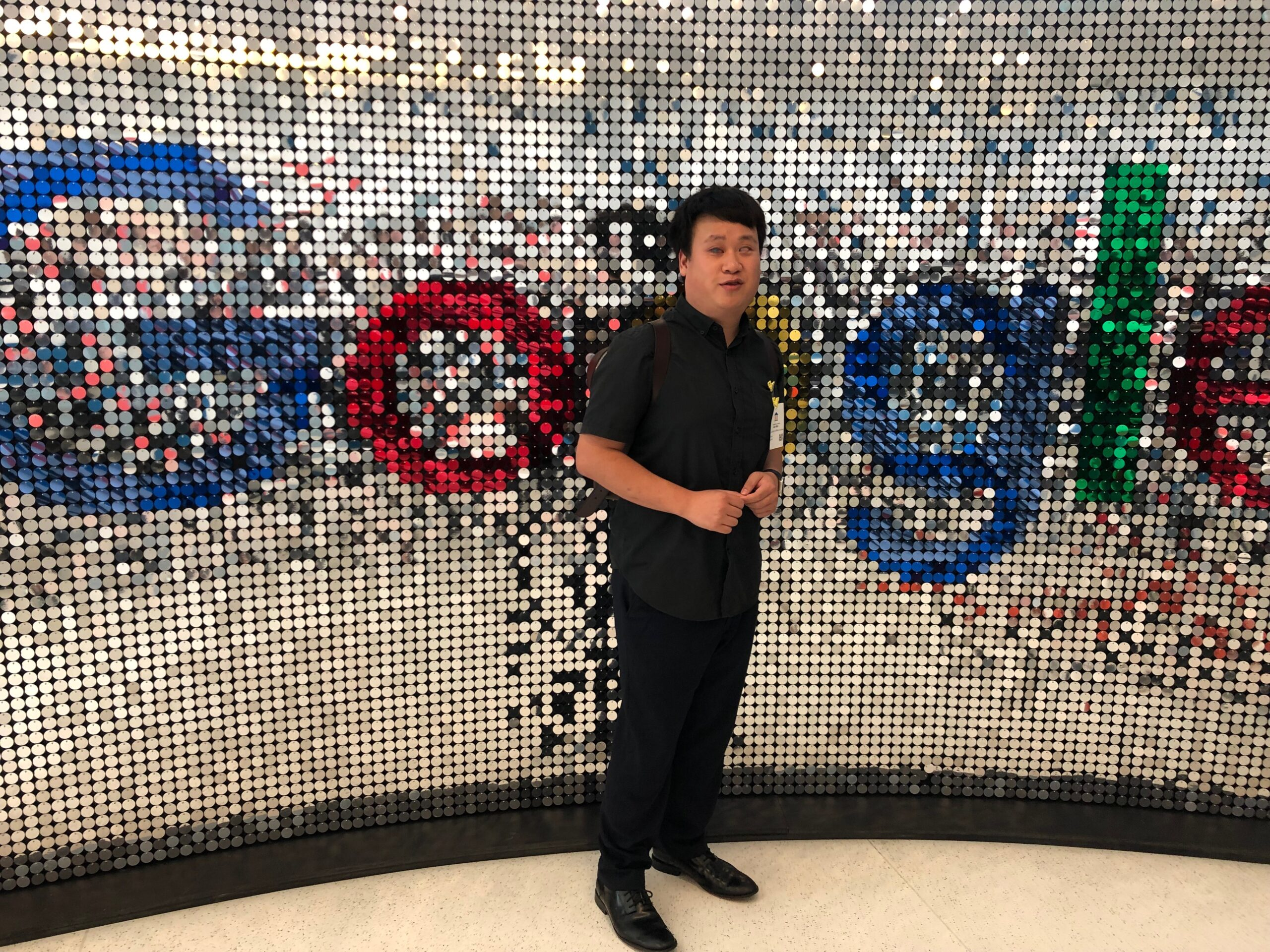 Dressed in a smart dark shirt, Alex stands in front of a Google logo